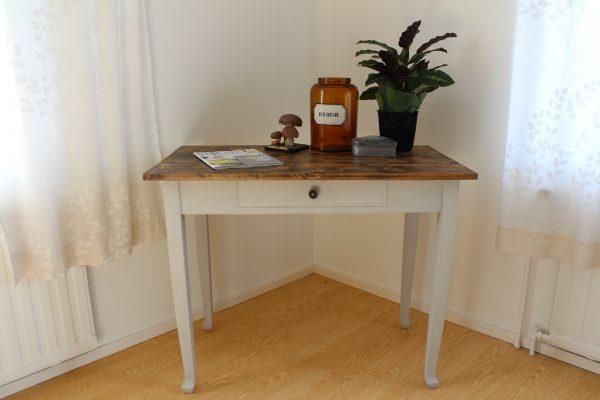 Gammalt flickbord med gråmålade ben och brunvaxad patinerad träskiva