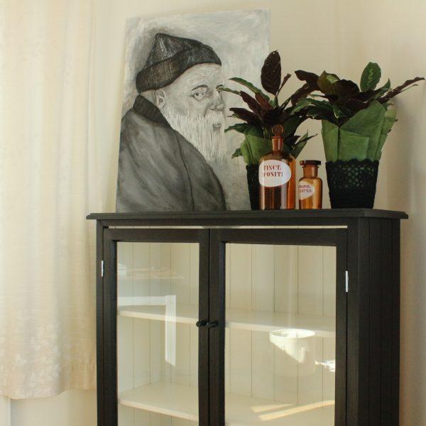 Vackert svart vitrinskåp med gammal gubbe tavla och gamla apoteksflaskor