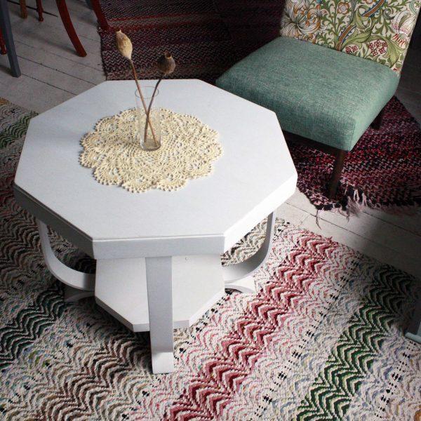 Ett grått soffbord på färgglada mattor med en liten vas.