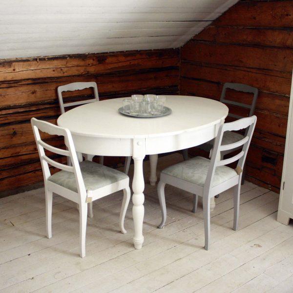Ovaltbord med fyra stolar framför stockvägg