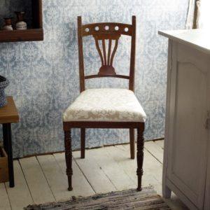stol i jugendstil framför mönstrad blå tapet