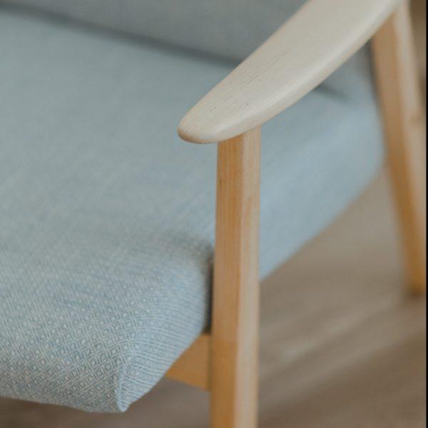 Askon nojatuolin käsinojasta yksityiskohta esittäen vaaleaa koivupuuta ja Trelliskankaan pientä kuviota